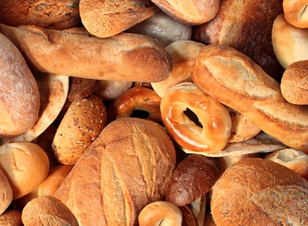 Bread background staple food concept with a group of baked goods from a bakery or home cooking made from whole wheat and grains with breads as pumpernickel pita focaccia bagel made from dough  photo