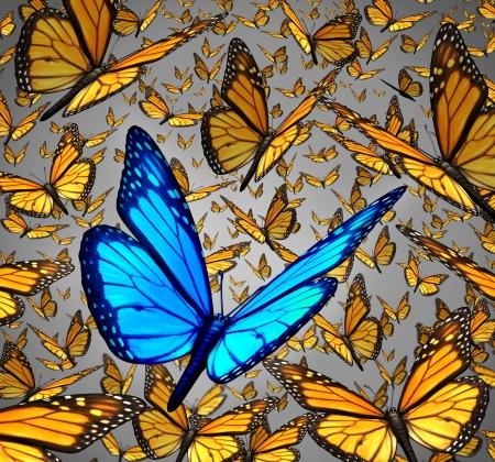 Nieuwe visie staande uit de menigte concept als een symbool van individualiteit en innovatief denken als een groep van Monarch vlinders vliegen met een enkele speciale insect kleur blauw als een icoon van creativiteit Stockfoto