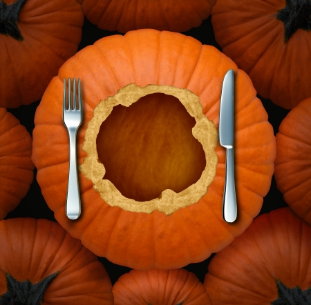Thanksgiving seasonal food celebration concept as an autumn cuisine symbol with an orange pumpkin cut as a circular dinner plate with a fork and knife table setting for gourmet fall food menu with a blank area as copy space  photo