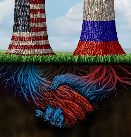 USA Russia cooperation and partnership business and diplomatic concept of working together for common interests as two growing trees with flags painted on with roots underground shaped as shaking human hands in agreement  photo