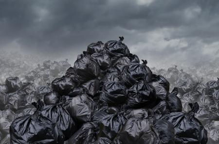 Garage dump concept met bergen van zwarte afvalzakken van afval met een onaangename geur in een oneindige stortplaats hoop landschap als achtergrond van milieuschade kwesties op een mistige donkere bewolkte scène Stockfoto