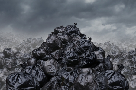 Garage dump concept with mountains of black waste bags of trash with an unpleasant smell  in an infinite landfill heap landscape as a background of environmental damage issues on a foggy  dark cloudy scene  Stockfoto