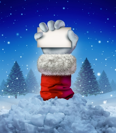Santa Claus winter sign as a hand holding a blank card emerging out of a pile of avalanche snow in a cold pine forest scene as a funny Christmas symbol and joyous seasonal holiday celebration message  Stock Photo - 24467831