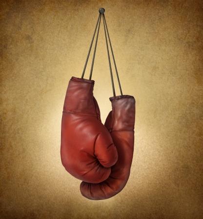 競技会: ビジネスや retirng 戦いをあきらめることまたは競争のための準備のスポーツ コンセプトとして、壁に釘のひもで、古いビンテージ グランジ背景上にぶら下がってボクシング グローブ