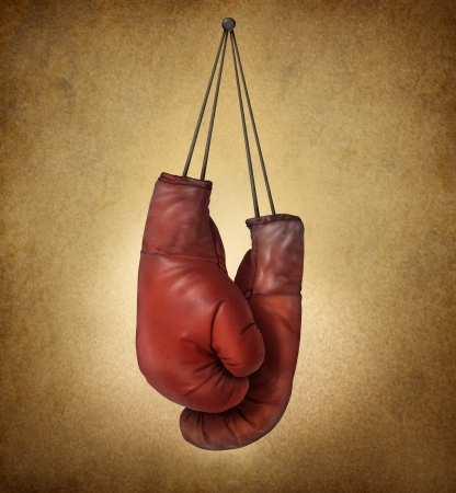 Boxing gloves hanging on an old vintage grunge background with laces nailed to a wall as a business or sport concept of retirng giving up the fight or preparing for competition