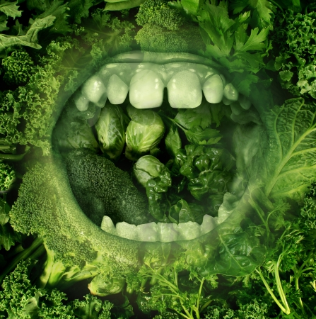 Eating green and healthy food concept with an open human mouth on a background of produce eating fresh vegetables as a symbol of good diet and nutrition and living a health lifestyle  photo