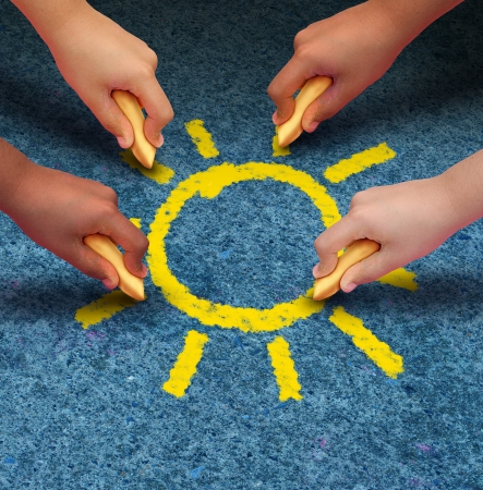 Community education and children learning and development concept with a group of hands representing ethnic groups of young people holding chalk cooperating together to draw a yellow sun shape as a metaphore for friendship