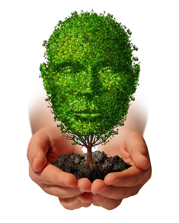 Nurture growth life development concept with a hand holding a green tree shaped as a front view human head as a caring metaphor