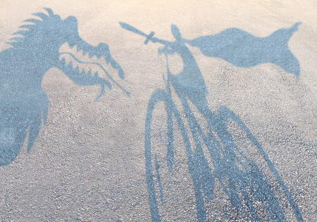 stories: Children imagination concept with cast shadows on a gravel floor of a superhero child wearing a cape on a bicycle slaying an imaginary dragon