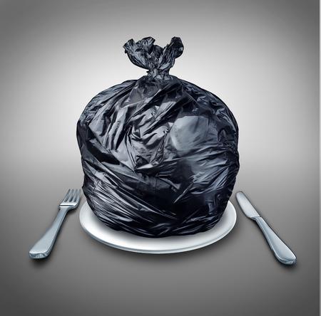 정크 푸드: 검은 플라스틱 쓰레기 칼 저녁 식사를 접시에 가방과 나쁜 다이어트 또는 강아지 가방 심볼에 대한 비유로 포크와 테이블 설정과 음식 쓰레기와 가난한 영양 개념