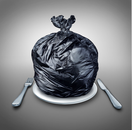 Food garbage and poor nutrition concept as a table setting with a black plastic garbage bag on a dinner plate with a knife and fork as a metaphor for a bad diet or doggy bag symbol  版權商用圖片