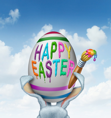 giant easter egg: Happy Easter greeting painted on a giant white egg with a paint brush being held by rabbit ears with detailed textured realistic fur as a fun spring symbol of holiday celebration on a sky background  Stock Photo