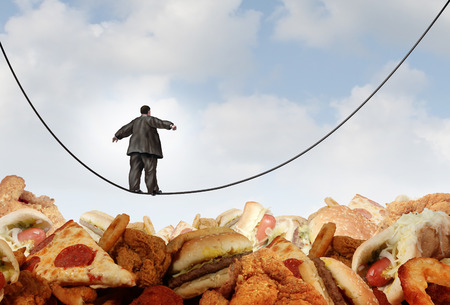an obese man walking on a tightrope high wire over mountains of greasy unhealthy junk food Stock Photo