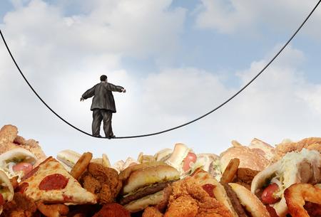 obesidad: un hombre obeso caminar sobre una cuerda floja cuerda floja sobre las montañas de grasienta comida chatarra poco saludable