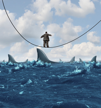 Vulnerable business concept  as an overweight unfit businessman walking on a sinking highwire with dangerouse sharks ready to attack as a metaphor for financial vulnerability in a competitive economic environment  Фото со стока