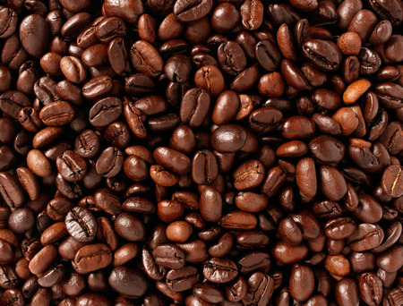 caffiene: Coffee beans background with roasted natural seeds for brewing espresso or cappuccino as a natural food concept with a java blend of different types of roasts from around the world