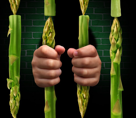 Restricted diet and calorie restriction food concept with prison bars made of asparagus vegetables and hands of a prisoner holding the jail as a dieting metaphor for the stress involved in healthy eating  Archivio Fotografico