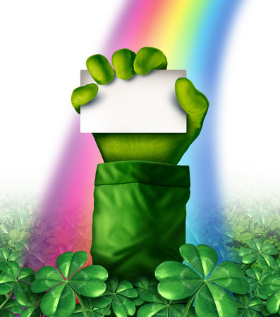 Saint Patricks day concept with a leprechaun hand in a green clover field holding up a blank white card as a rainbow glows upon the character as a symbol for spring and Irish celebration  photo