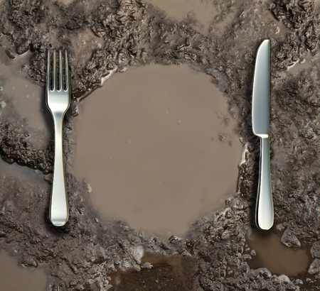 food inspection: Food sanitation concept and global poverty symbol as a wet ground with a mud puddle of dirty water shaped as a dinner plate with a silver fork and knife as a metaphor for contamination health risk  Stock Photo