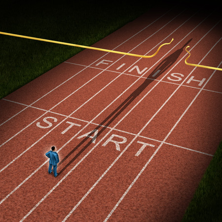 Forward thinking business concept for success acceleration with a businessman standing on the start line in a track and feild path with a cast shadow breaking through the finish line ribbon for victory