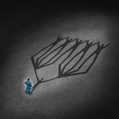 Liderazgo de equipos y el concepto de líder de negocios con un hombre de negocios de pie con una sombra proyectada de un grupo de la red conectada de empleados y socios que trabajan como una metáfora de la sociedad trabajo en equipo Foto de archivo