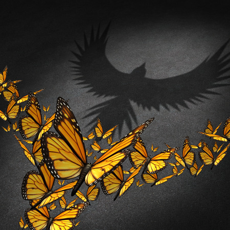 Power of teamwork business concept as a group of monarch butterflies getting together to cast a shadow of a strong eagle as a metaphor for partnership communication success through network connections cooperation