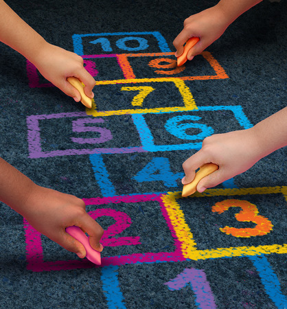 hopscotch: Community development education and children learning concept with a group of hands representing ethnic groups of young people holding chalk cooperating together as friends to draw a playground hopscotch game