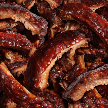 Ribs grilled barbecue meat with a close up view of a group of delicious cooked marinated spare rib as  gourmet food for dinner at a restaurant or backyard BBQ grill  photo