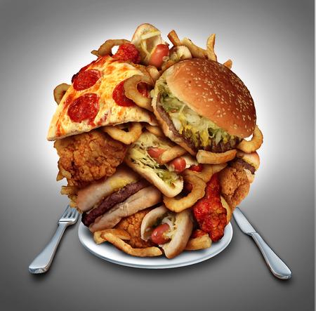 Fast food dieet concept geserveerd op een bord als een berg van vettig gebakken restaurant nemen als uienringen hamburger en hotdogs met gebakken kip frieten en pizza als een symbool van dwangmatig overeten en dieet verleiding resulteert in ongezonde nutr Stockfoto
