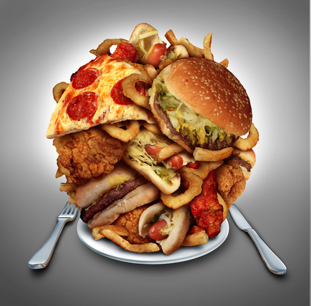 Fast food diet concept served on a plate as a mountain of greasy fried restaurant take out as onion rings burger and hot dogs with fried chicken french fries and pizza as a symbol of compulsive overeating and dieting temptation resulting in unhealthy nutr Banco de Imagens