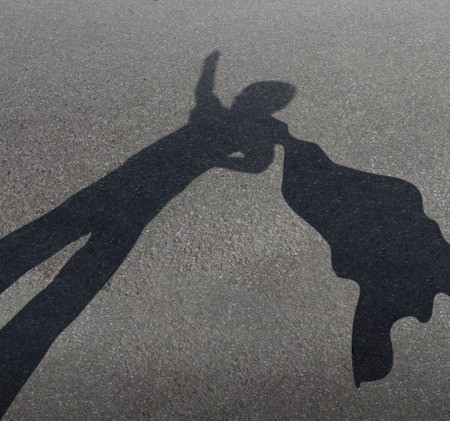 shadow: Superhero kid pretending to be a powerful courageous hero with a cape flying in the wind as a fun childhood play symbol for the fertile imagination of a child as a cast shadow on an urban asphalt road  Stock Photo
