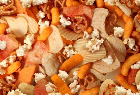 Snacks achtergrond met zoute knapperige lekkernijen als chips en kaas op smaak soesjes gefrituurd of gebakken voedsel als pretzels pop corn en nacho's als symbool van diverse party mix voorgerecht Stockfoto