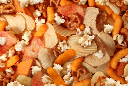 Snacks background with salty crunchy treats as potato chips and cheese flavored puffs fried or baked food as pretzels pop corn and nachos as a symbol of assorted party mix appetizer