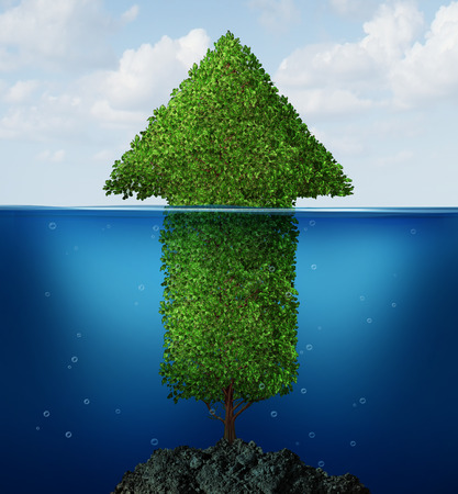 Business recovery concept as an arrow tree drowning underwater emerging to the surface rising out of the ocean as a financial symbol of  economic growth return  Stock Photo
