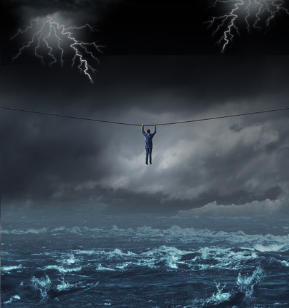 surviving: Surviving the storm business concept with a businessman hanging on to a tightrope crossing over dangerous water as a concept and metaphor for conquering adversity and overcoming challenges