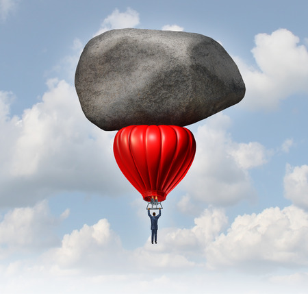 Leadership power and business challenges concept as a businessman piloting a red hot air balloon with a huge heavy rock slowing the rise as an obstacle to career and financial success