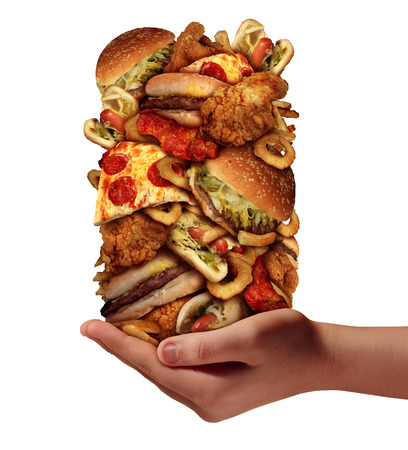 Over eating and compulsive indulgence of fast food concept as a hand holding up a huge stack of junk food as hamburgers hotdogs and french fries as an unhealthy diet nd bad nutrition symbol isolated on a white background