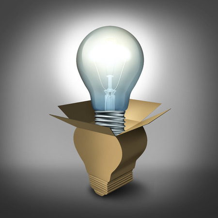creativity: Think outside the box concept as a cardboard package shaped as a bulb with an illuminated light emerging as a symbol of new creativity and innovation success  Stock Photo