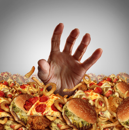 Obesity and overweight concept as the hand of a person emerging from a heap of unhealthy fast food and desperately reaching out for diet and dieting help as a symbol of bad nutrition proplems