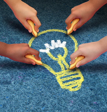 innovative: Community ideas education concept as a group of children hands holding chalk drawing a lightbulb icon on a pavement floor as a symbol of hope and team success  Stock Photo