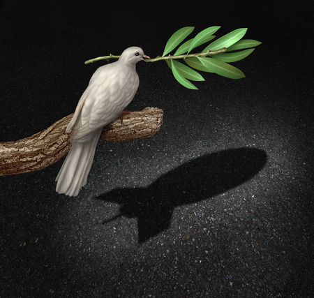 Risk of war concept as a freedom peace dove holding an olive branch casting a shadow that is shaped as a bomb as a symbol of  the danger of warfare caused by hatred and political posturing. Foto de archivo