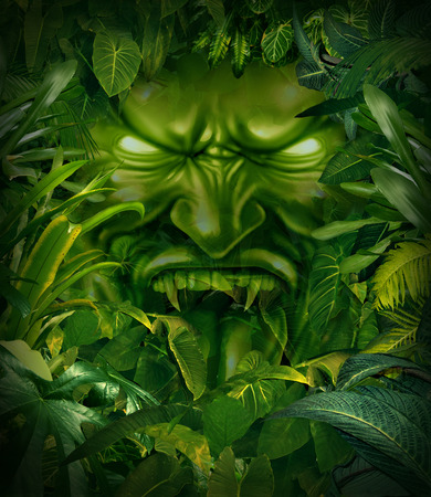 Jungle fear nightmare concept as a scary monster head emerging out from a dark tropical rain forest as a symbol of risk and exploration danger. 스톡 콘텐츠