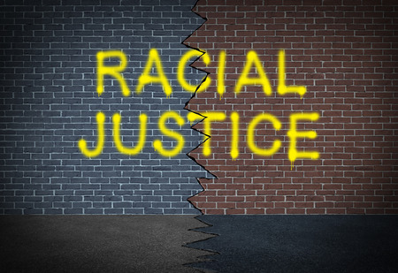 Racial justice and fighting discrimination concept and race relations social issue symbol as graffitti writing on a two toned brick wall as an icon of working together for civil rights and community cooperation between different ethnic groups  Stock Photo