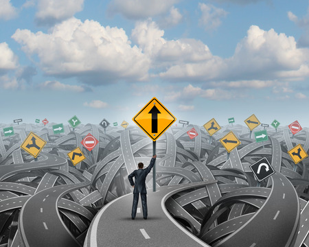 Success direction with a confident businessman standing on a group of tangled streets holding up a traffic sign with an upward arrow as a symbol for clear belief and conviction to a path of prosperity overcoming confusion and fear  Foto de archivo