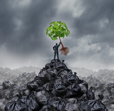 business environment: Green businessman concept as a man on top of a mountain heap of garbage holding up a green leaf tree with roots as an environment and conservation icon for waste management or a new healthy beginning.