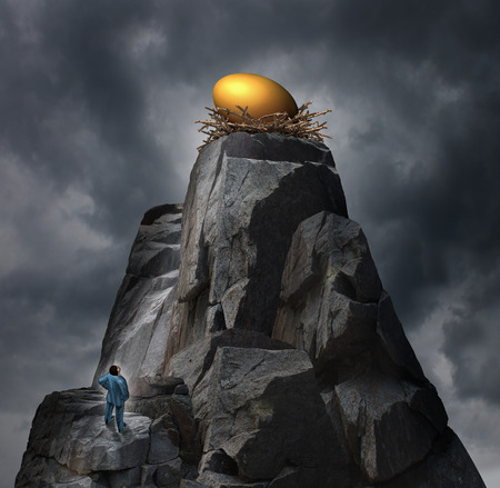 Golden nest egg concept as a retirement plan metaphor with a man standing at the bottom of a rock cliff thinking of a strategy to achieve his financial investment goal perched at the top of a dangerous the high mountain. Archivio Fotografico