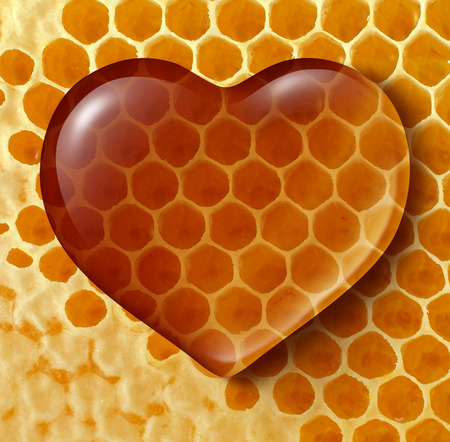 Healthy food love concept as liquid honey shaped as a heart on a honeycomb or honey comb background created by bees as a healthy lifestyle sweetener symbol of fresh natural organic nutrition from nature.