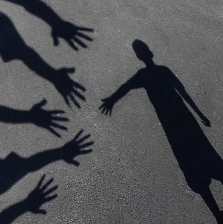 Community support and helping  children concept with shadows of a group of extended adult hands offering help or therapy to a child in need as an education symbol of social responsibility t for needy kids and teacher guidance to students who need extra ca photo