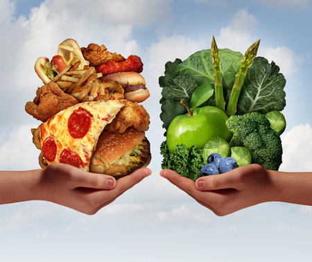 junk: Nutrition choice and diet decision concept and eating choices dilemma between healthy good fresh fruit and vegetables or greasy cholesterol rich fast food with two hands holding food trying to decide what to eat.