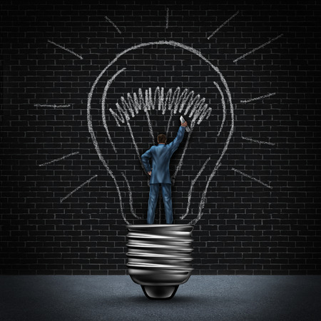 Light bulb man business concept as a businessman standing in a light base and drawing an illuminated  photo